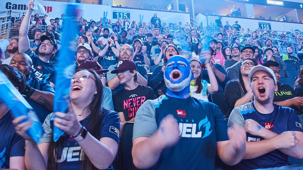 An image of Overwatch League fans at the venue. There's a guy with face-paint on and he looks awesome.